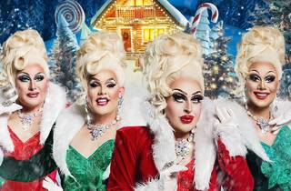 Drag queens dressed in Christmas costumes pose in a winter wonderland.