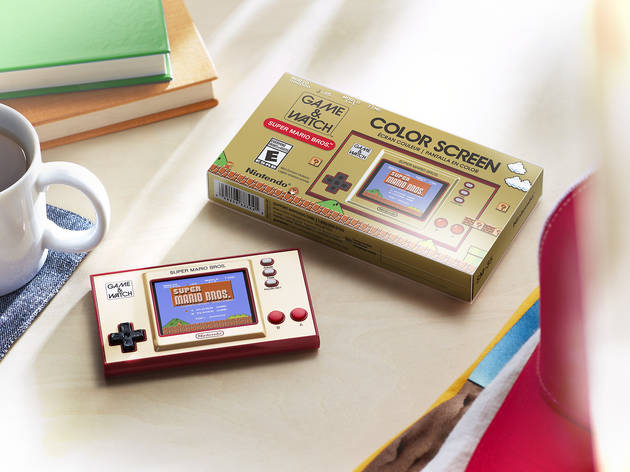 A Nintendo Game & Watch: Super Mario Bros console on a table with its gold box beside it