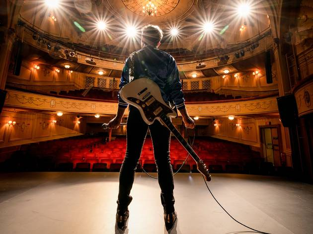 A man wearing an electric guitar looking out into an empty theatre