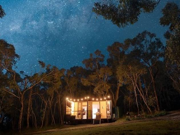 Tiny house in the forest lit up with fairylights