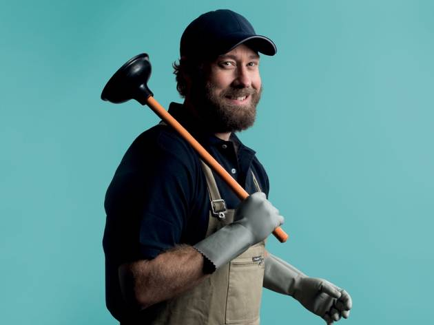 A man in overalls cap and short shirt with hairy arms holds a toilet plunger aloft