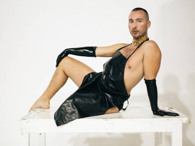 Model poses on white table, wears black latex apron and gloves, nothing else.