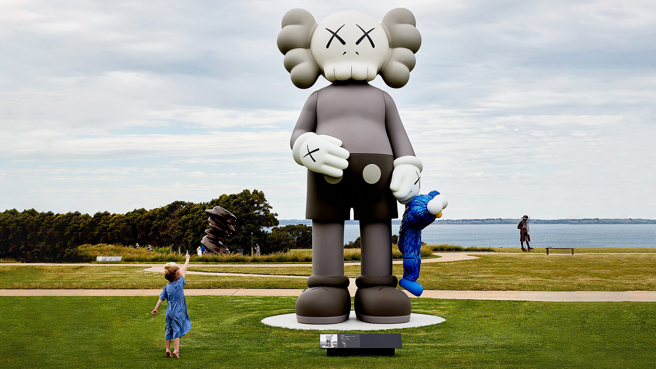 A huge grey sculpture of a pop art skull character on a peninsula. A small child reaches up to it