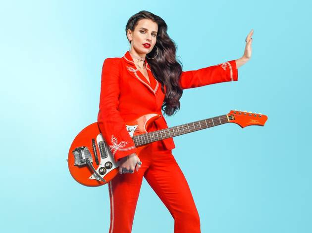 Imogen clark in a red pant suit with red guitar against a pale blue backdrop