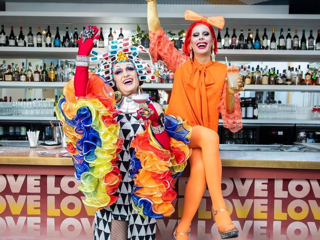 Two drag queens pose by bar holding cocktails