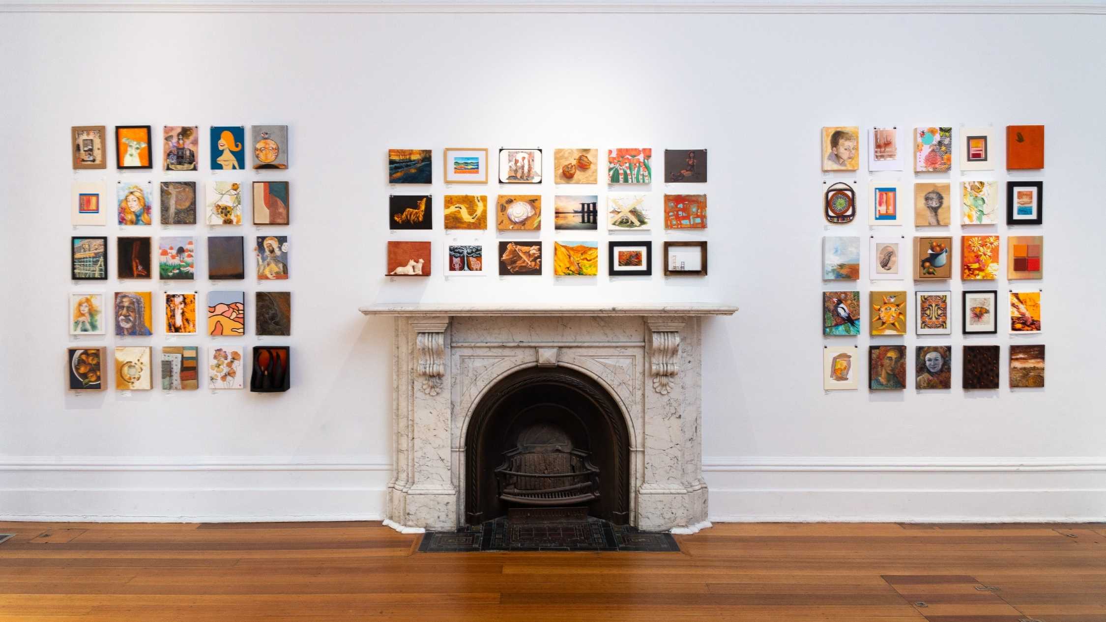 Dozens of small artworks hung on a white wall over a timber floor and white marble fireplace
