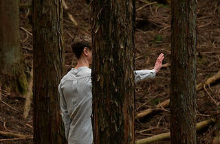 A man person with short hair stands in a forest with their arm and palm outstretched