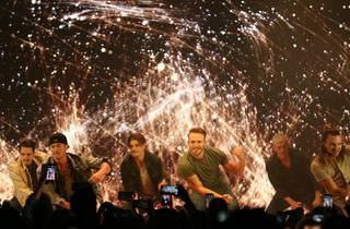 The Magic Mike Live hotties kneel in front of a firework-like light show