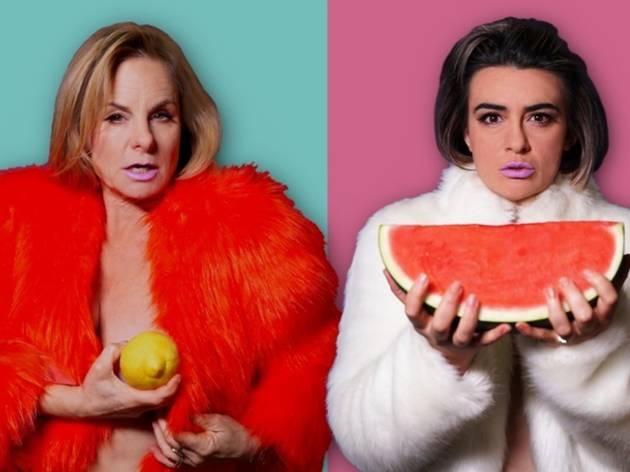 Rebecca Massey and Sheridan Harbridge in fake fur coats holding a lemon and a watermelon