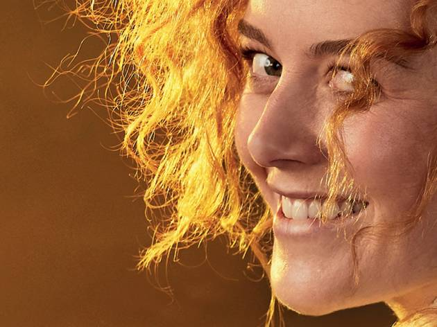A red-haired Nikki Shiels looking over her shoulder, close-up, as Sybylla in Belvoir's My Brilliant Career