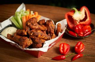 Chicken wing box with chillis nearby