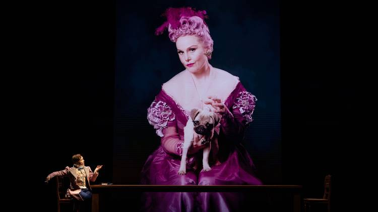 Eryn Jean Norvial in pink ress holding apug, and in a suit, looking up at the big screen image of herself in another roleSydney Theatre Company 2020