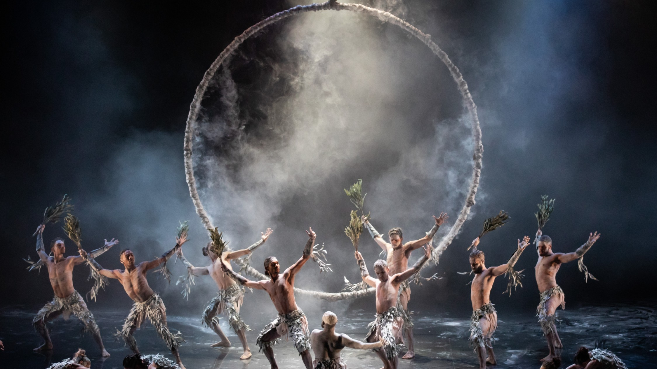 Bangarra dancers perform in smoke in front of a huge circle hung above the stage
