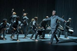 David Byrne in grey suit dances barefoot with his diverse American Utopia bnad