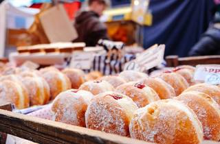 Trays of doughnuts at market stall.