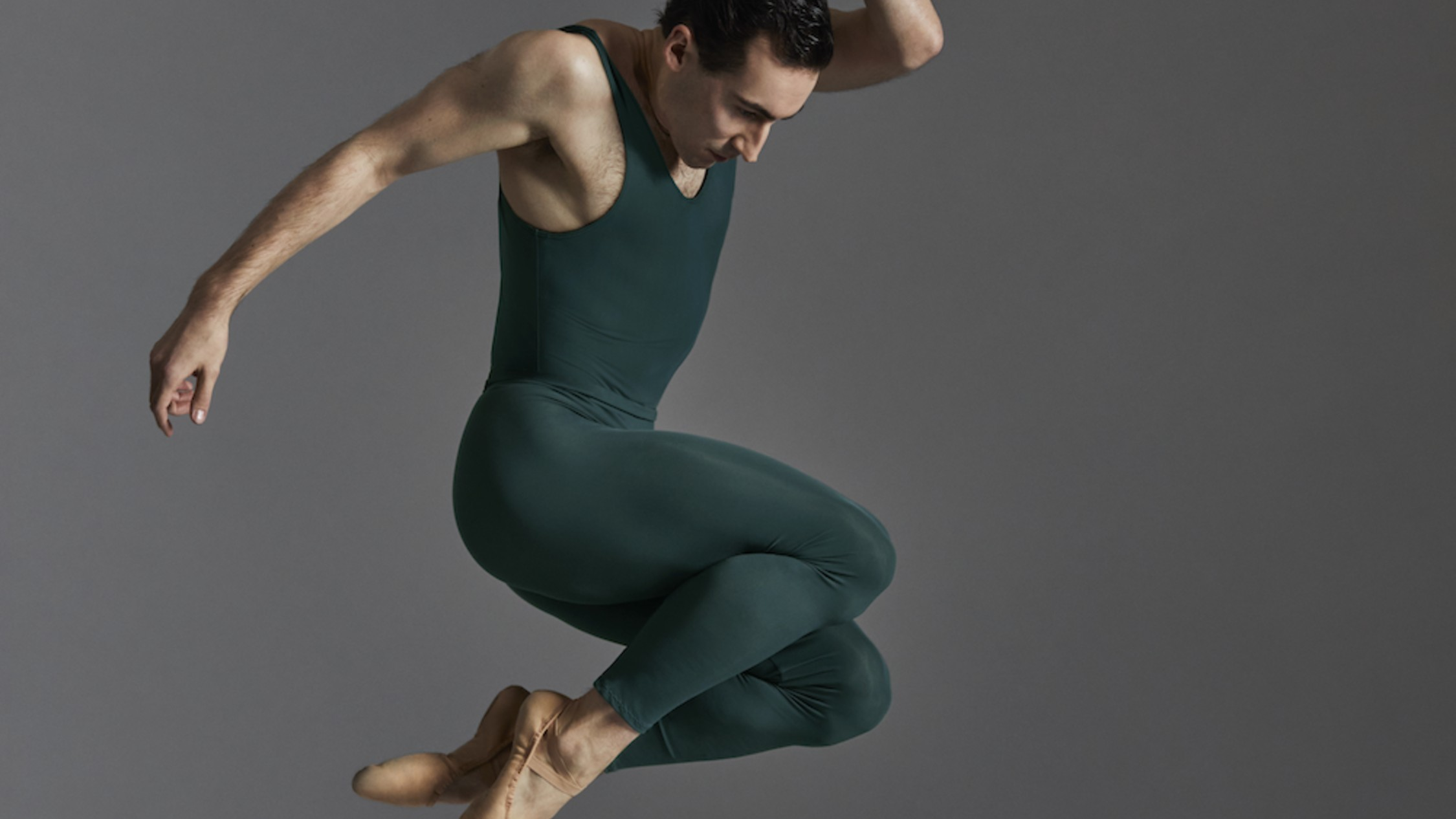 A male dancer in a green jump suit mid-leap