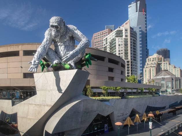A 9 metre chimpanzee sculpture sits on a structure with Arts Centre Melbourne in the background
