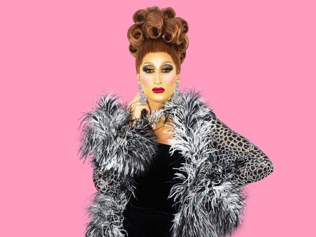 Drag queen Prada Clutch poses in feather trimmed gown.