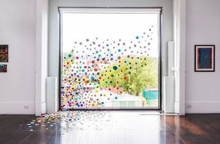 A shot from inside Arising. Paintings hang on a white wall either side of a ceiling-length window covered with colourful circles