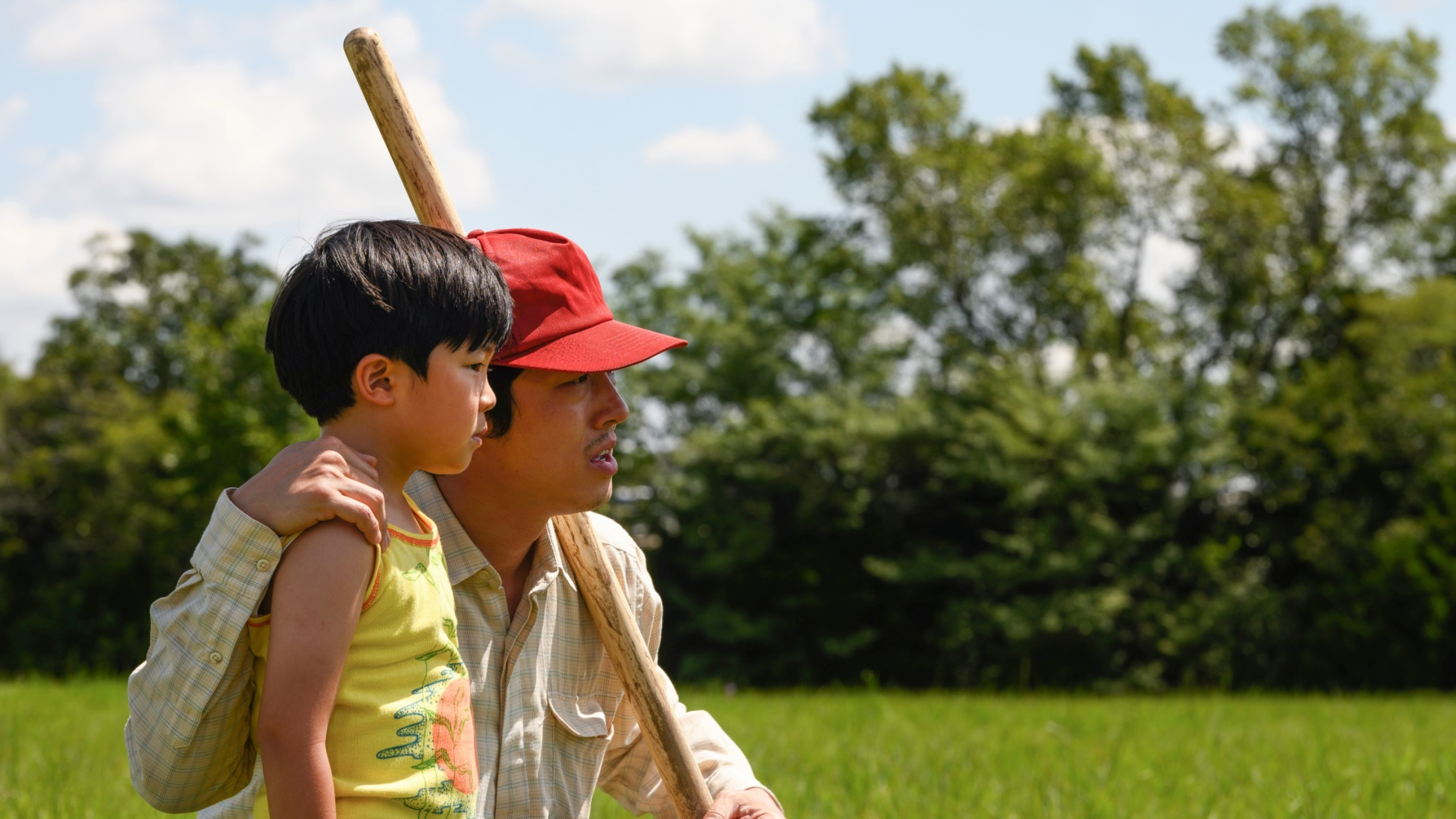 A man in a red cap with a big stick places a hand on his young son's shoulder