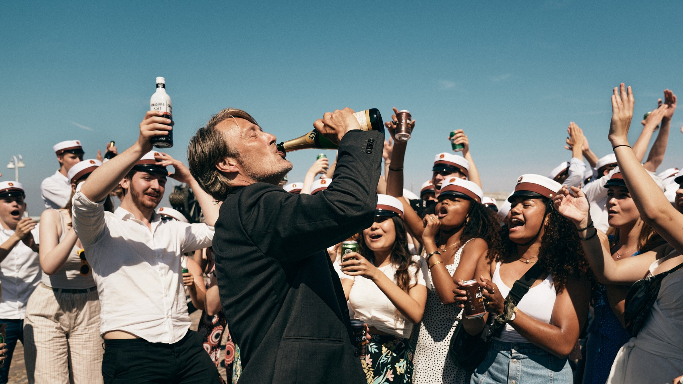 A man drinks from a champagne bottle while drunk teenagers celebrate all around him