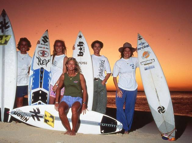 Women pose with surfboards at sunset