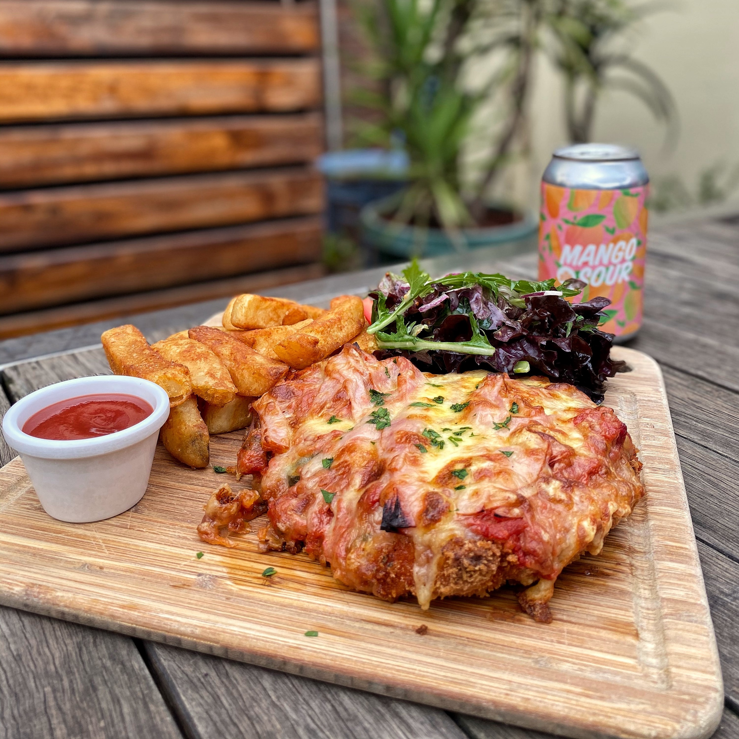 Chicken parma with chips, salad, tomato sauce and a beer