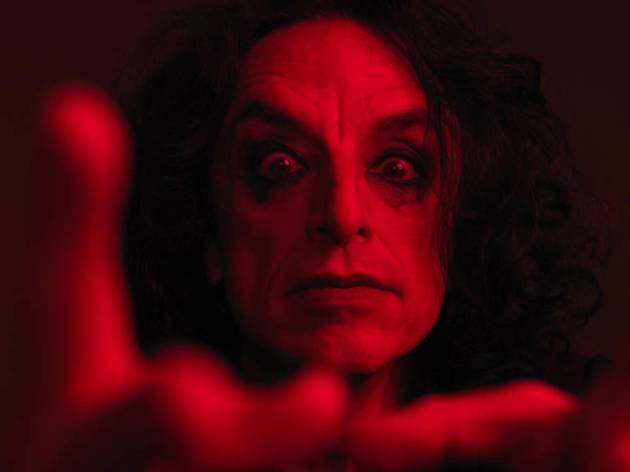 A close-up of Paul Capsis with dark eye makeup, bathed in red light