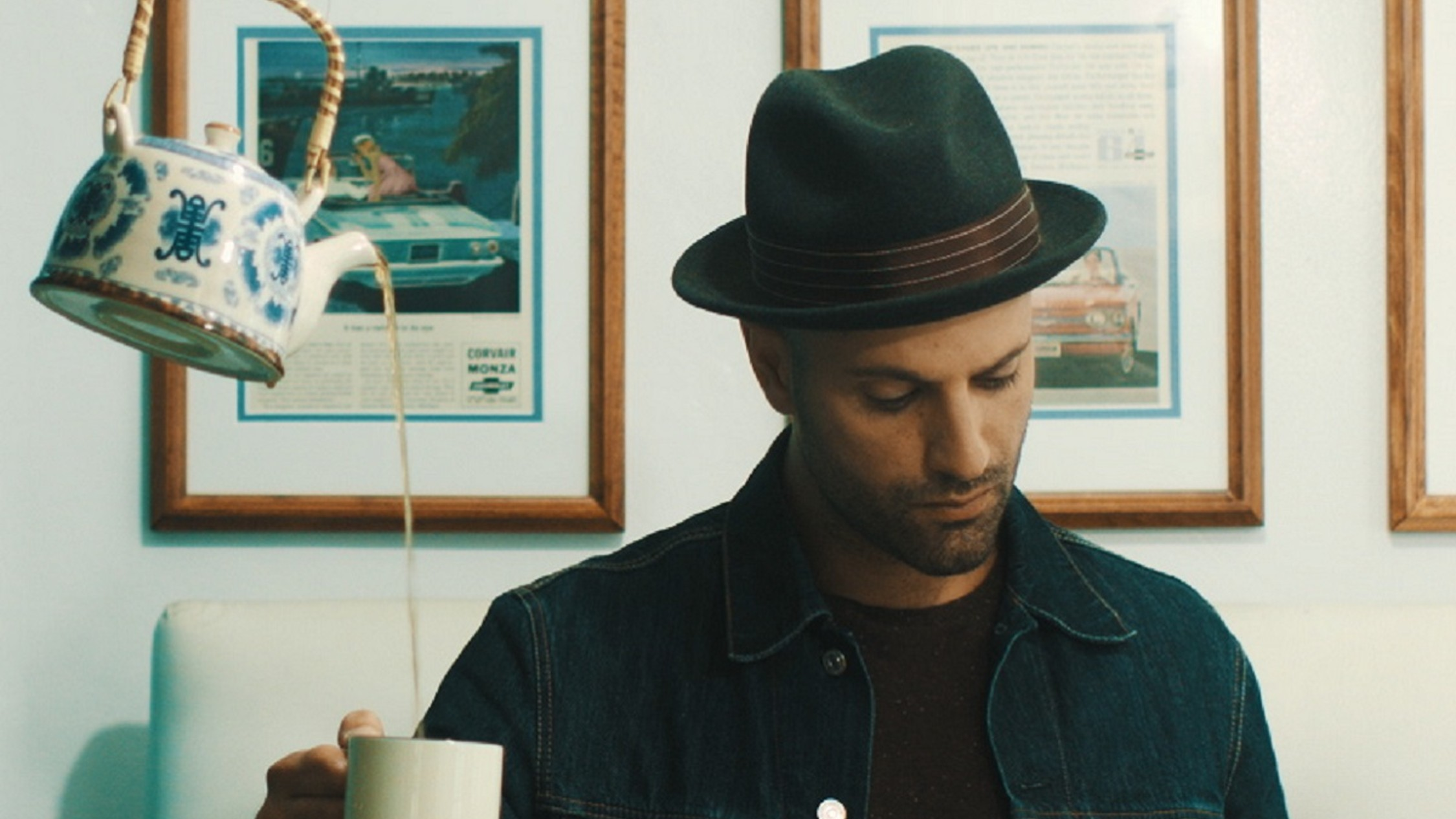 Magician James galea in a denim jacket and hat with a floating kettle filling his tea cup
