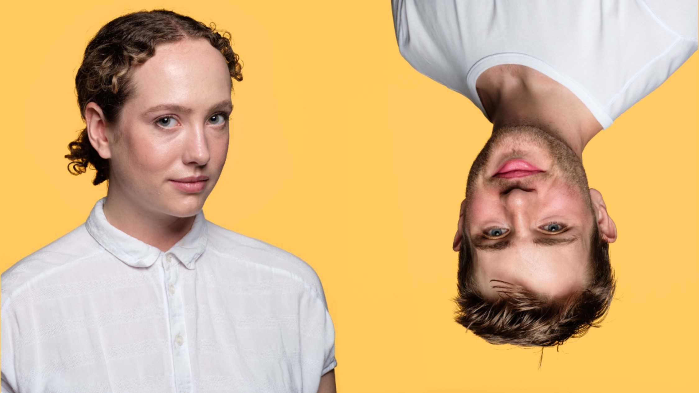 a man and a woman in white shirts, him upside down, against a yellow backdrop