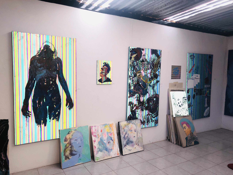 Interior de taller artístico con paredes rosa y pinturas colgadas