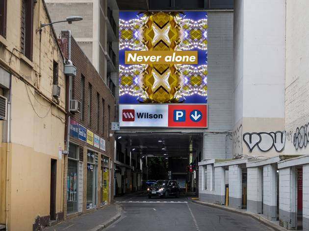 """Artist render of a billboard with """"Never Alone"""" on it about the Wilsons Carpark on Bourke St"""