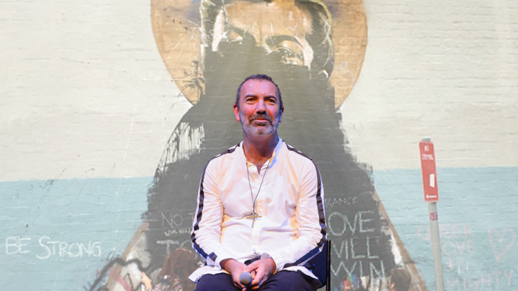 Paul Mac sits on stage, he is superimposed onto an image of a defaced mural.