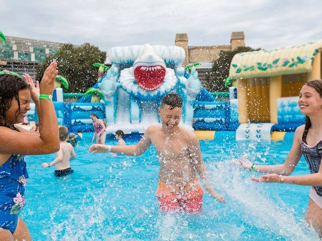 Three kids playing at an inflatable water park