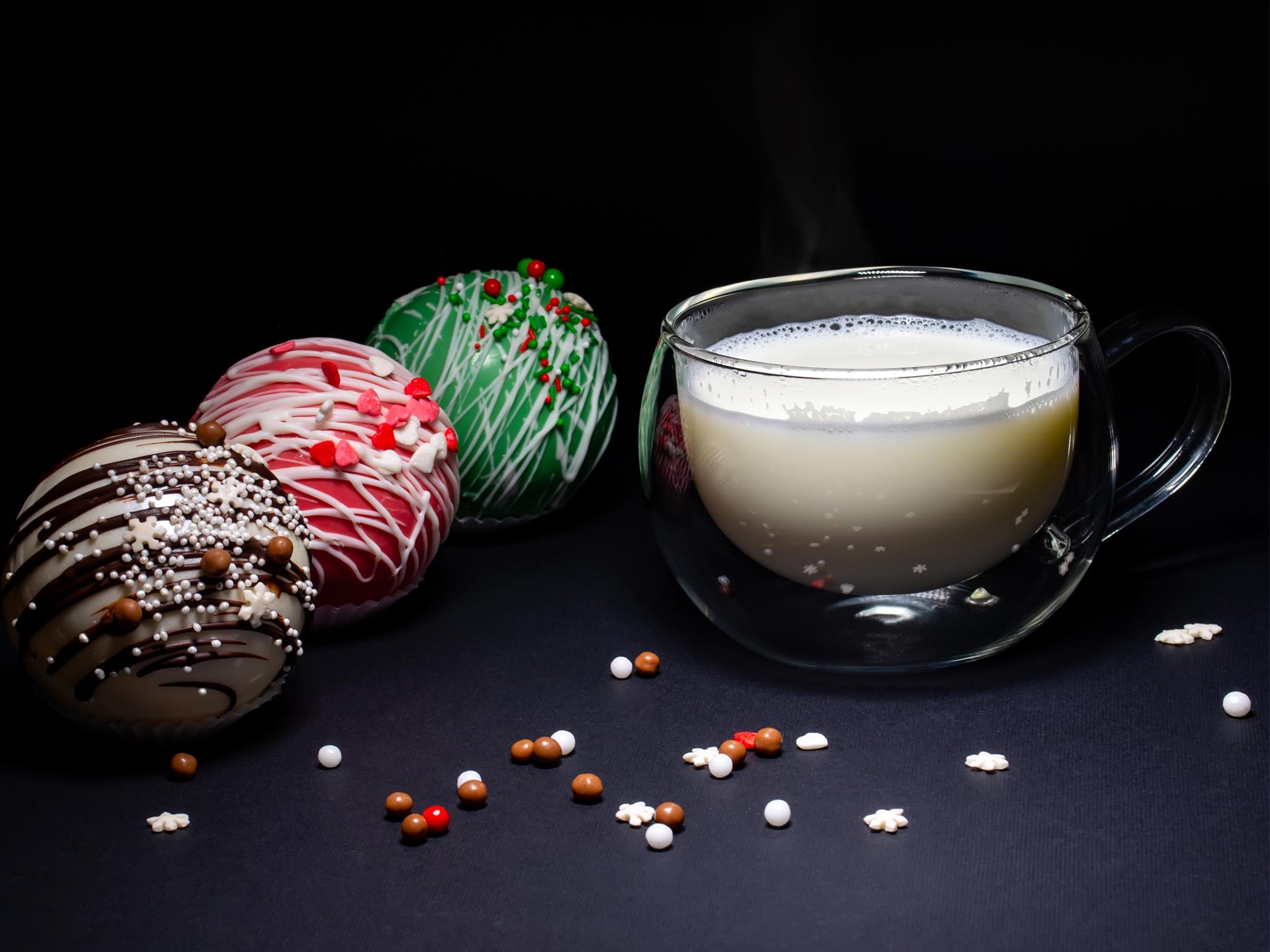 Taza de leche caliente con bolas de chocolate a un lado