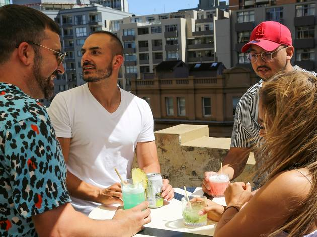 People enjoy cocktails on a rooftop