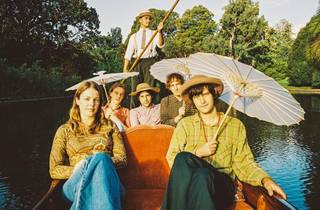 The band Bananagun sits on a gondola in a lake with parasols and golden afternoon light