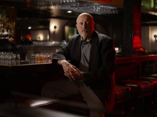 A detective propped up at a dark red-lit bar
