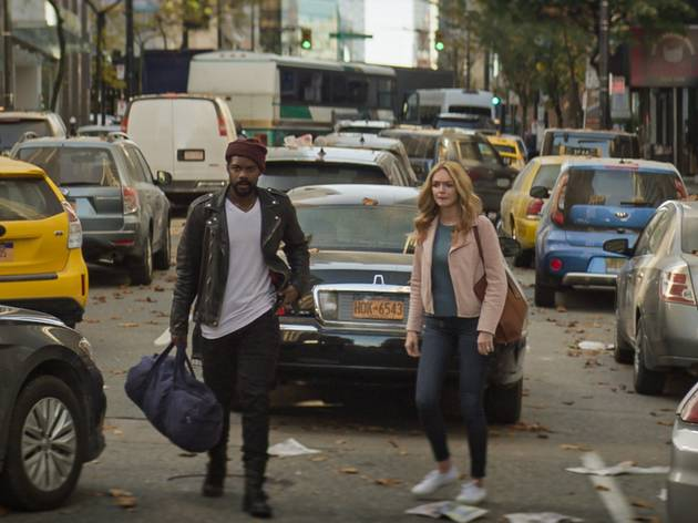 A man and a woman traverse an abandonned car-strewn road