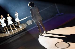 A shot of the actor playing Evonne Goolagong  from behind, facing competitors across the net
