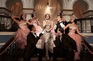 The Merry Widow cast in Deco-inspired costumes, in opulent surrounds