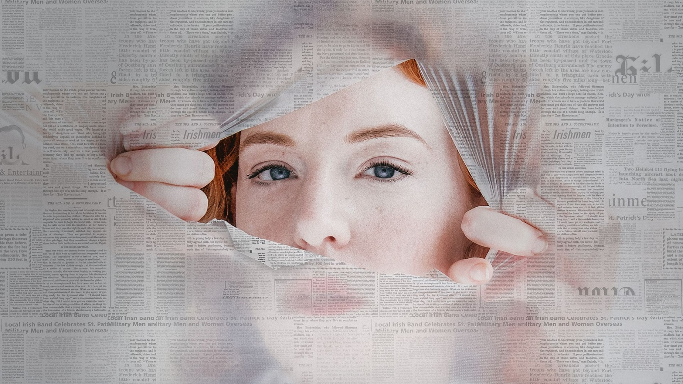 A red-headed woman peering through a torn hole in a newspaper