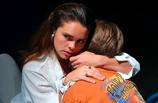 A woman in a white shirt with dark holds an man in an orange shirt