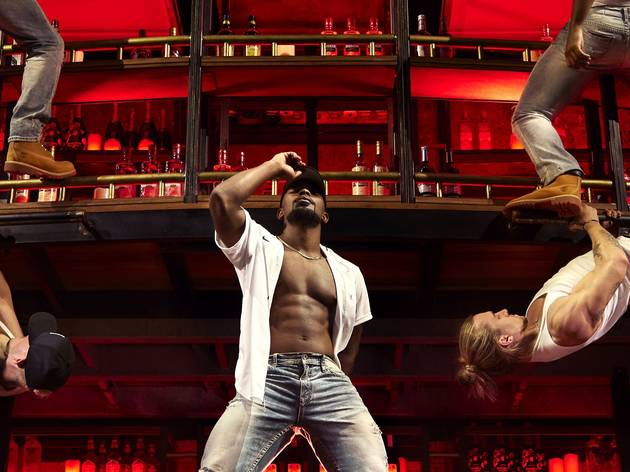 Ripped dancers in jeans and open white shirts gyrate on a climbing frame bar