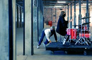 Tina Havelock Stevens in black beating a drum set on a moving platform pulled by Ivey Wawn