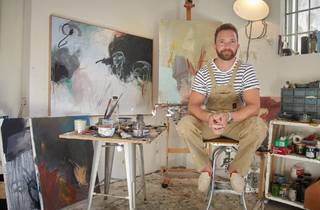 Tim Draxl in a stripey T and painters overalls in his studios surrounded by oil paintings