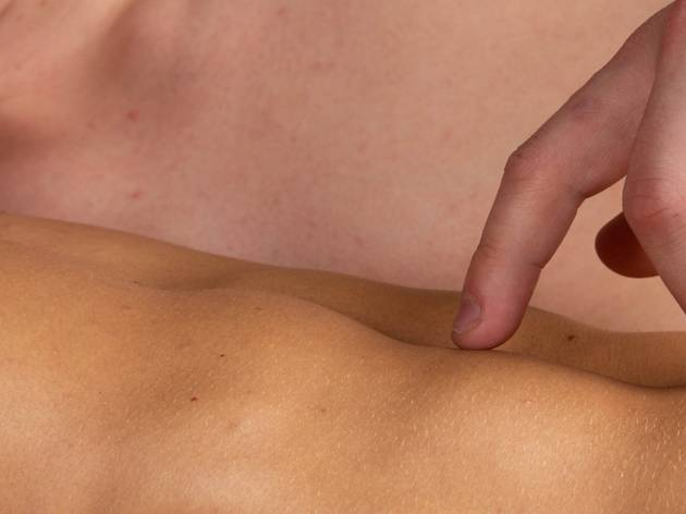 A close up of two naked male torsos, one man walks his fingers across the other's abs