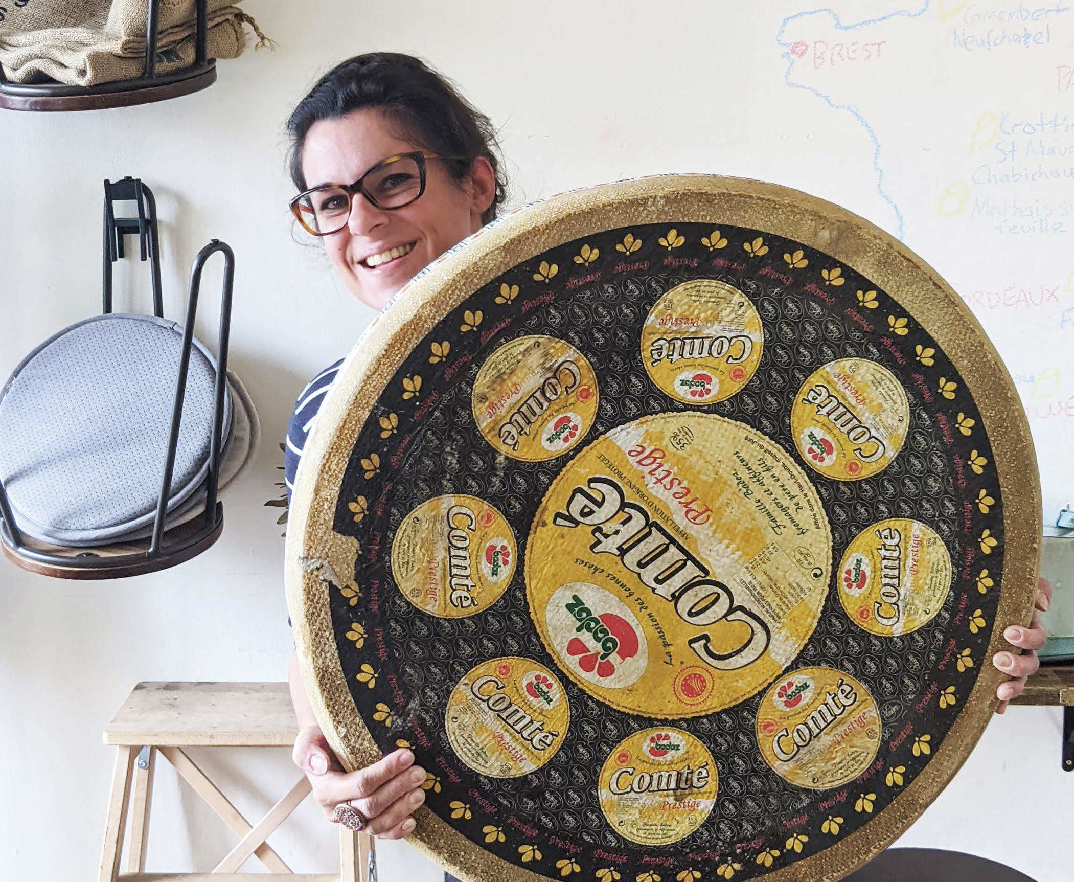 A woman holding a giant wheel of comte cheese