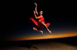Sermsah Sermsah in an orange wrap leaps in the desert at night