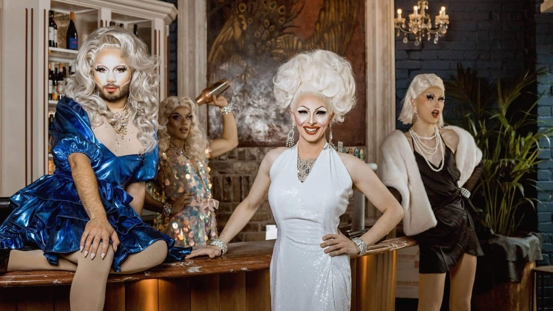 Drag queens pose on bar